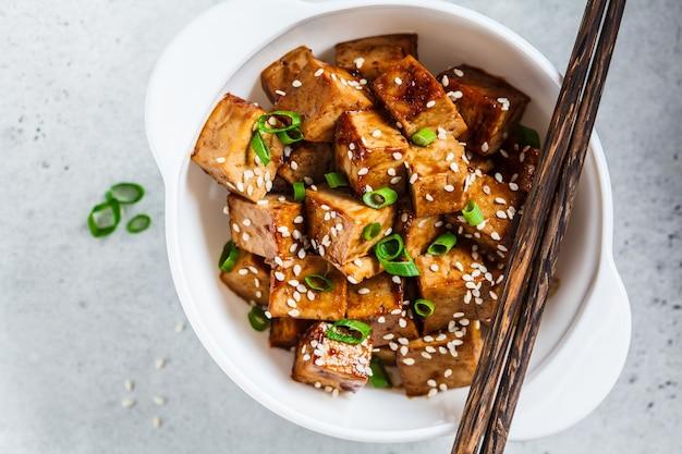 Gebraden tofu in teriyakisaus in witte kom, hoogste mening. veganistisch eten concept. Premium Foto
