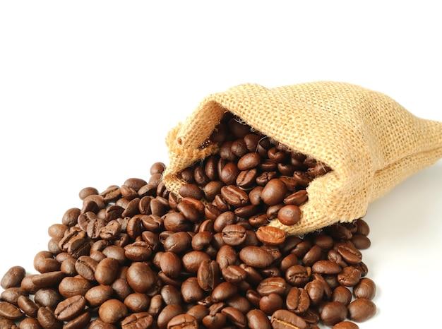 Gebrande koffiebonen die van geïsoleerde jutezak worden verspreid Premium Foto