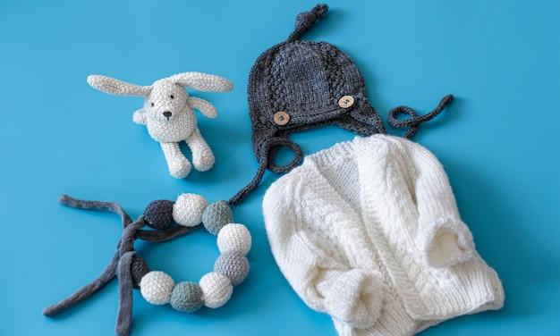 Gebreide babykleertjes en accessoires op blauw Gratis Foto