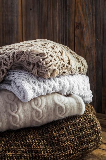 Gebreide gezellige trui liggend op houten muur Gratis Foto