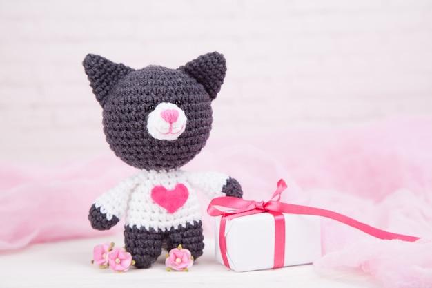 Gebreide kat met een hart. st. valentijnsdag decor. gebreide speelgoed, amigurumi. valentijnsdag wenskaart. Premium Foto