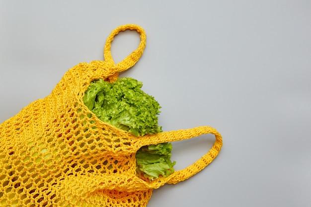 Gebreide tas met salade op een grijze achtergrond met kopie ruimte. winkelen eten met milieuvriendelijke tas. Premium Foto