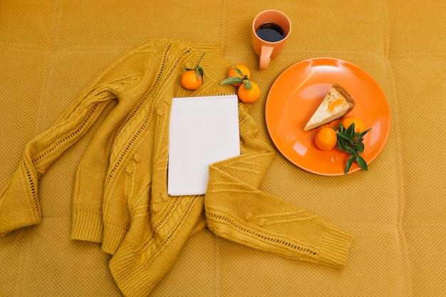 Gebreide trui, kopje koffie, cheesecake, mandarijnen, notitieboekje op oranje tafel Gratis Foto