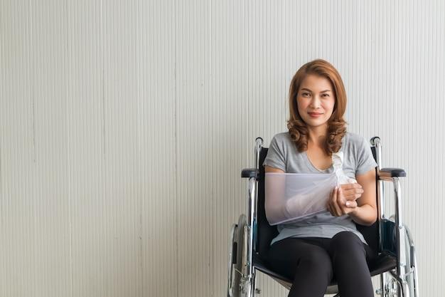 Gebroken arm aziatische vrouw met arm sling gesponsord in haar handen zittend op een rolstoel ideeën voor ongevallen verwondingen en gezondheidszorg studio geschoten op wit Premium Foto
