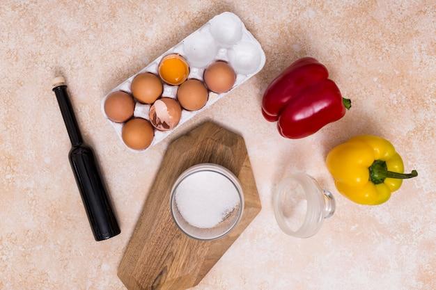 Gebroken eierschalen; olie fles; suikerkruik en groene paprika's op geweven achtergrond Gratis Foto