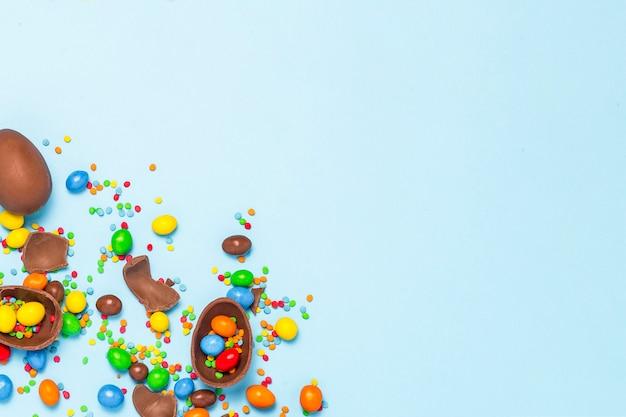 Gebroken en hele chocolade paaseieren, veelkleurige snoepjes op blauwe achtergrond. concept het vieren van pasen, pasen-decoraties, zoek naar snoepjes voor paashaas. plat lag, bovenaanzicht. kopieer ruimte. Premium Foto