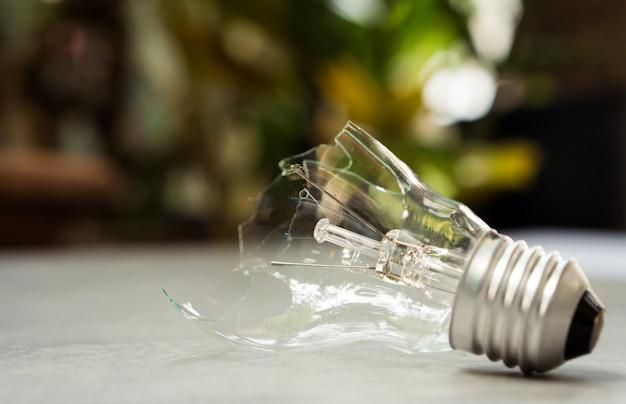 Gebroken gloeilamp op aardachtergrond, energieoplossing voor het oplossen van milieuprobleem Premium Foto
