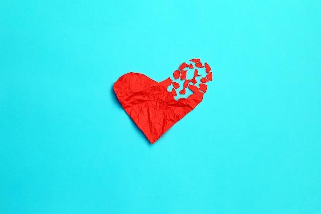 Gebroken hart uiteenvallen concept scheiding en scheiding pictogram. rood verfrommeld papier in de vorm van een gescheurde liefde Premium Foto
