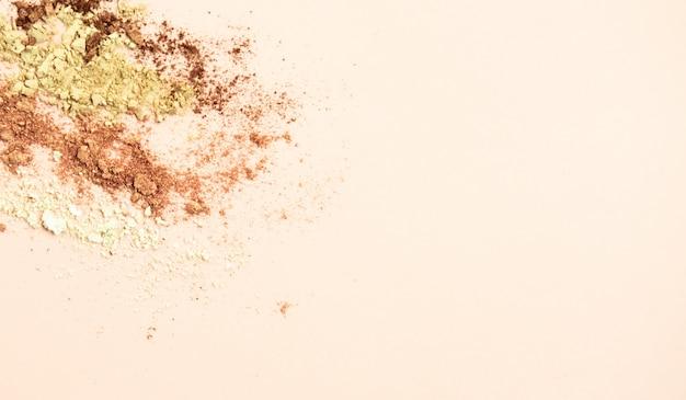 Gebroken kleurrijke oogschaduwen maken omhoog palet op pastelkleur oranje achtergrond. Premium Foto