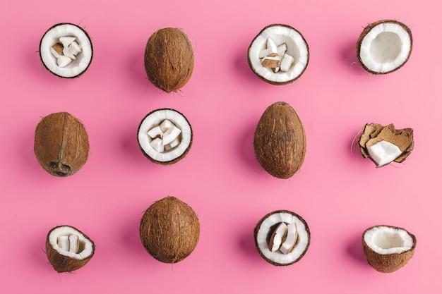 Gebroken kokosnoot stukken op fel roze, bovenaanzicht, kopie ruimte Premium Foto