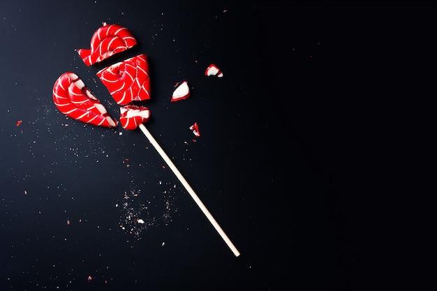 Gebroken lolly in vorm van hart op donker met exemplaarruimte Premium Foto