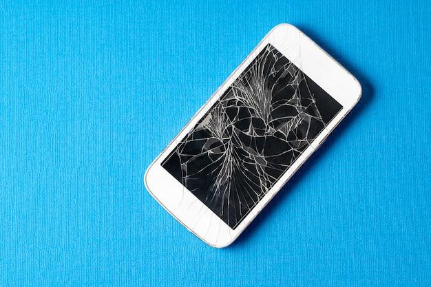 Gebroken mobiele telefoon met gebarsten display op een blauwe achtergrond. Premium Foto