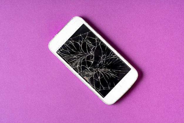 Gebroken mobiele telefoon met gebarsten vertoning op purpere achtergrond. Premium Foto