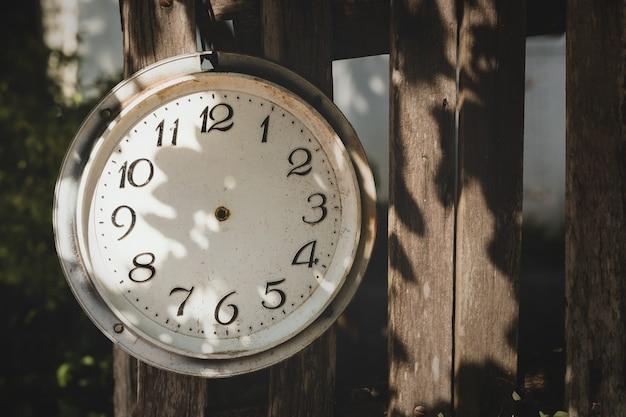 Gebroken oude uitstekende klok zonder pijlen in verlaten tuin Premium Foto