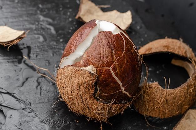 Gebroken rijpe kokosnoot op zwarte leisteen Premium Foto