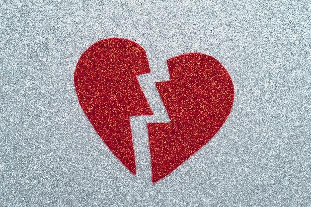 Gebroken rood hart op grijs glitterpapier, een break-up-concept. applique met klatergoud. een symbool van liefde, valentijnsdag, romantische gevoelens en emoties. Premium Foto