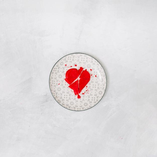 Gebroken rood hart op plaat Gratis Foto