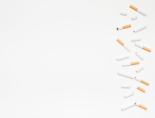 Gebroken sigaretten die op bodem over geïsoleerde op witte achtergrond worden geschikt Gratis Foto