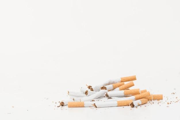 Gebroken sigaretten die op witte achtergrond worden geïsoleerd Gratis Foto