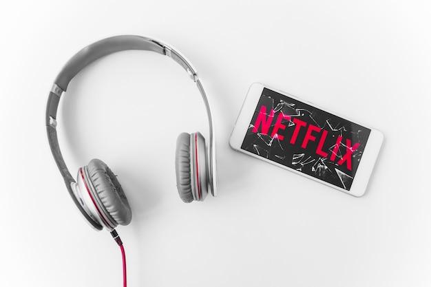 Gebroken smartphone met netflix-logo in de buurt van een hoofdtelefoon Gratis Foto
