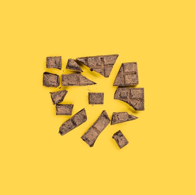 Gebroken stukjes chocolade op gele ondergrond Gratis Foto