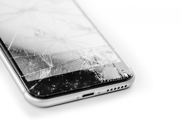 Gebroken telefoon die op witte achtergrond wordt geïsoleerd Premium Foto