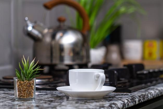 Gebrouwen thee in een witte kop en een fluitketel op gasfornuis in de keuken thuis. tijd voor ontbijt Premium Foto
