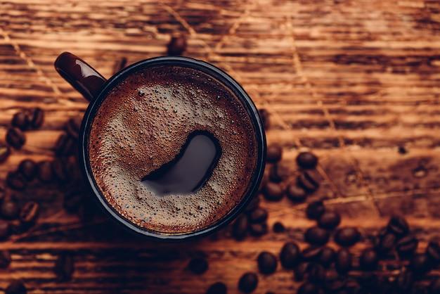 Gebrouwen zwarte koffie in metalen mok over houten oppervlak Premium Foto