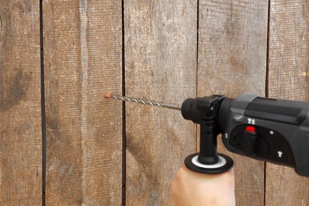 Gebruik een hamerboor om de muur te boren Premium Foto