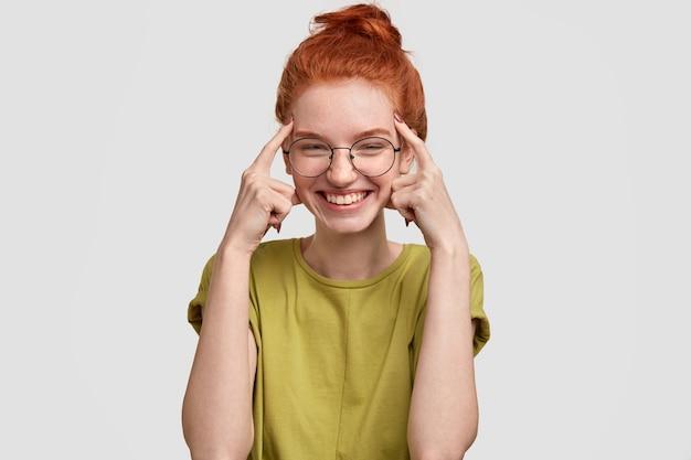 Gebruik je hersens. gelukkig roodharig meisje houdt beide wijsvingers op de slapen, probeert na te denken voordat ze dom handelt, lacht vrolijk, gekleed in casual zomerkleding, staat tegen een witte muur. Gratis Foto