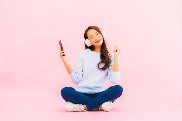Gebruik van de portret mooie jonge aziatische vrouw slimme mobiele telefoon met hoofdtelefoon om muziek op roze muur te luisteren Gratis Foto