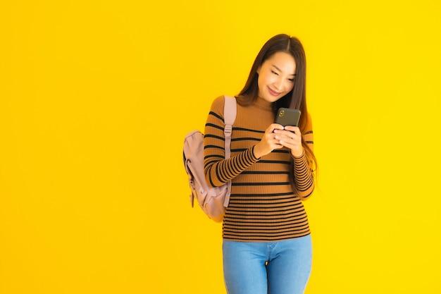 Gebruikt de portret mooie jonge aziatische vrouw met bagpack smartphone Gratis Foto