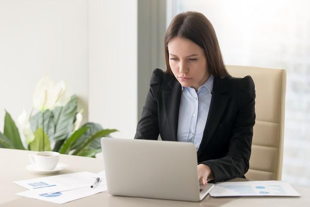 Geconcentreerd ernstig onderneemster die rapport maakt, dat met laptop in bureau werkt Gratis Foto