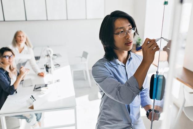 Geconcentreerde aziatische manager tekening grafiek op flip-over tijdens presentatie. binnenportret van chinese beambte die iets op wit bord schrijven terwijl zijn vrouwelijke collega's toekijken. Gratis Foto