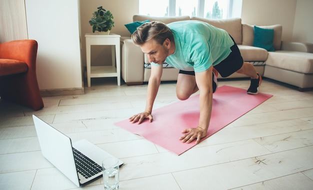 Geconcentreerde blonde blanke man doet rekoefeningen op het yogatapijt terwijl hij naar de laptop kijkt met een waterglas in de buurt Premium Foto