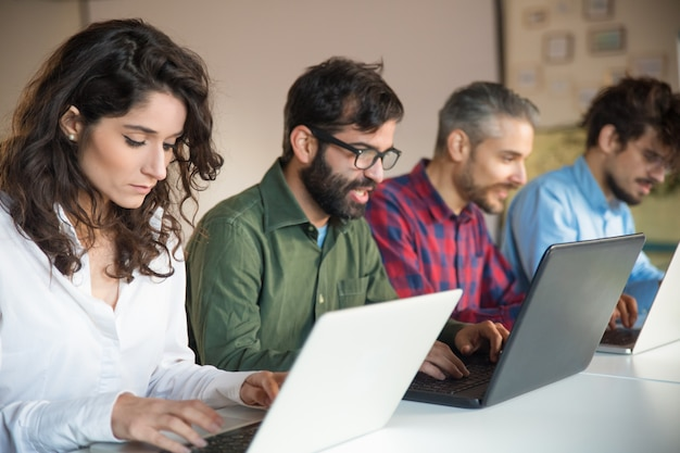 Geconcentreerde collega's die laptops met behulp van bij vergaderingslijst Gratis Foto