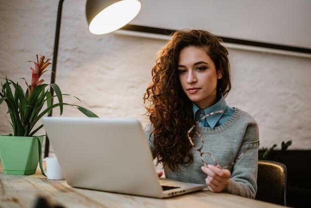 Geconcentreerde jonge mooie onderneemster die aan laptop in helder modern bureau werkt. Premium Foto