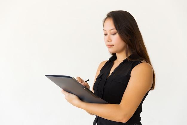 Geconcentreerde jonge vrouw die in omslag schrijft Gratis Foto