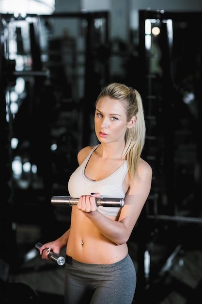 Geconcentreerde jonge vrouw gewichtheffen Gratis Foto