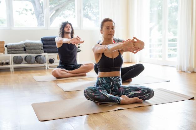 Geconcentreerde kerel en meisje die yoga in gymnastiek doen Gratis Foto
