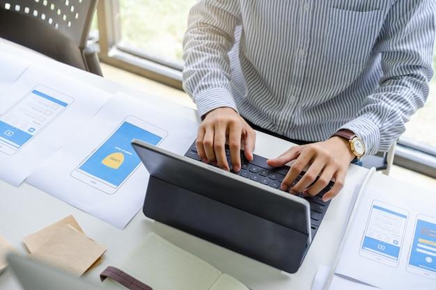 Geconcentreerde man in casual werken of typen op slimme toetsenbordtablet voor het ontwerpen, coderen, programmeren van mobiele applicatie. Premium Foto