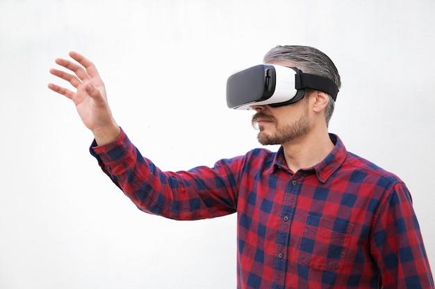 Geconcentreerde man van middelbare leeftijd in vr-headset aanraken van lucht Gratis Foto