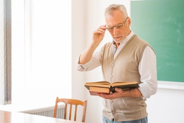 Geconcentreerde mannelijke professor in glazen die boek in klaslokaal lezen Gratis Foto