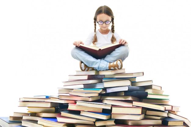 Geconcentreerde meisje omringd door boeken Gratis Foto