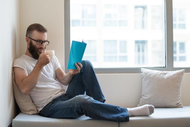 Geconcentreerde mens die in glazen koffie drinkt terwijl het lezen van boek Gratis Foto