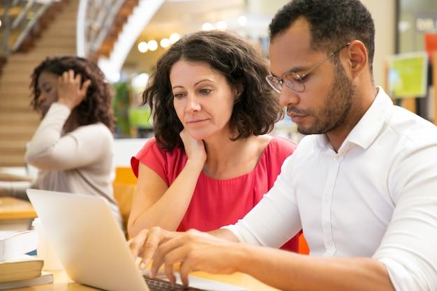Geconcentreerde mensen die informatie lezen van laptop Gratis Foto
