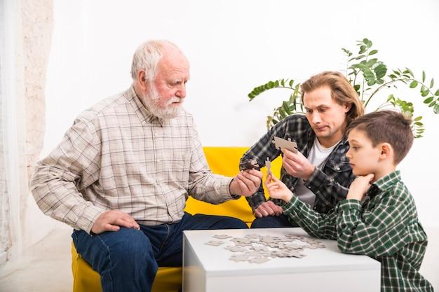 Geconcentreerde multi-generational familie die puzzel samen assembleren Gratis Foto