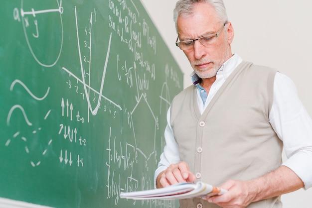 Geconcentreerde oude wiskundeleraar die leerboek bekijkt Gratis Foto