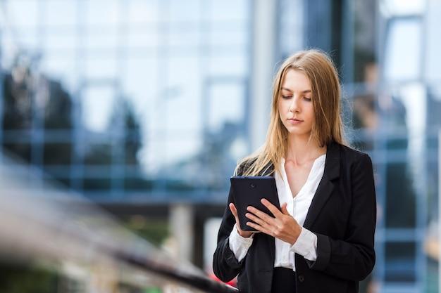 Geconcentreerde vrouw die een tablet gebruikt Gratis Foto