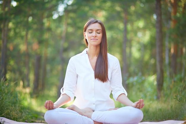 Geconcentreerde vrouw mediteren in de natuur Gratis Foto